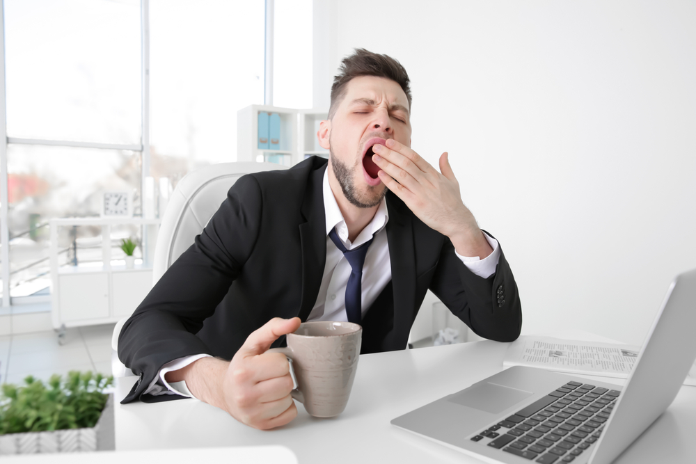 Tired,Business,Man,Yawning,At,Workplace,In,Office