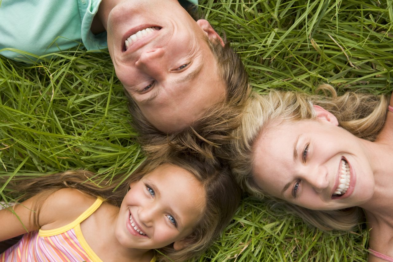 Family lying in grass smiling