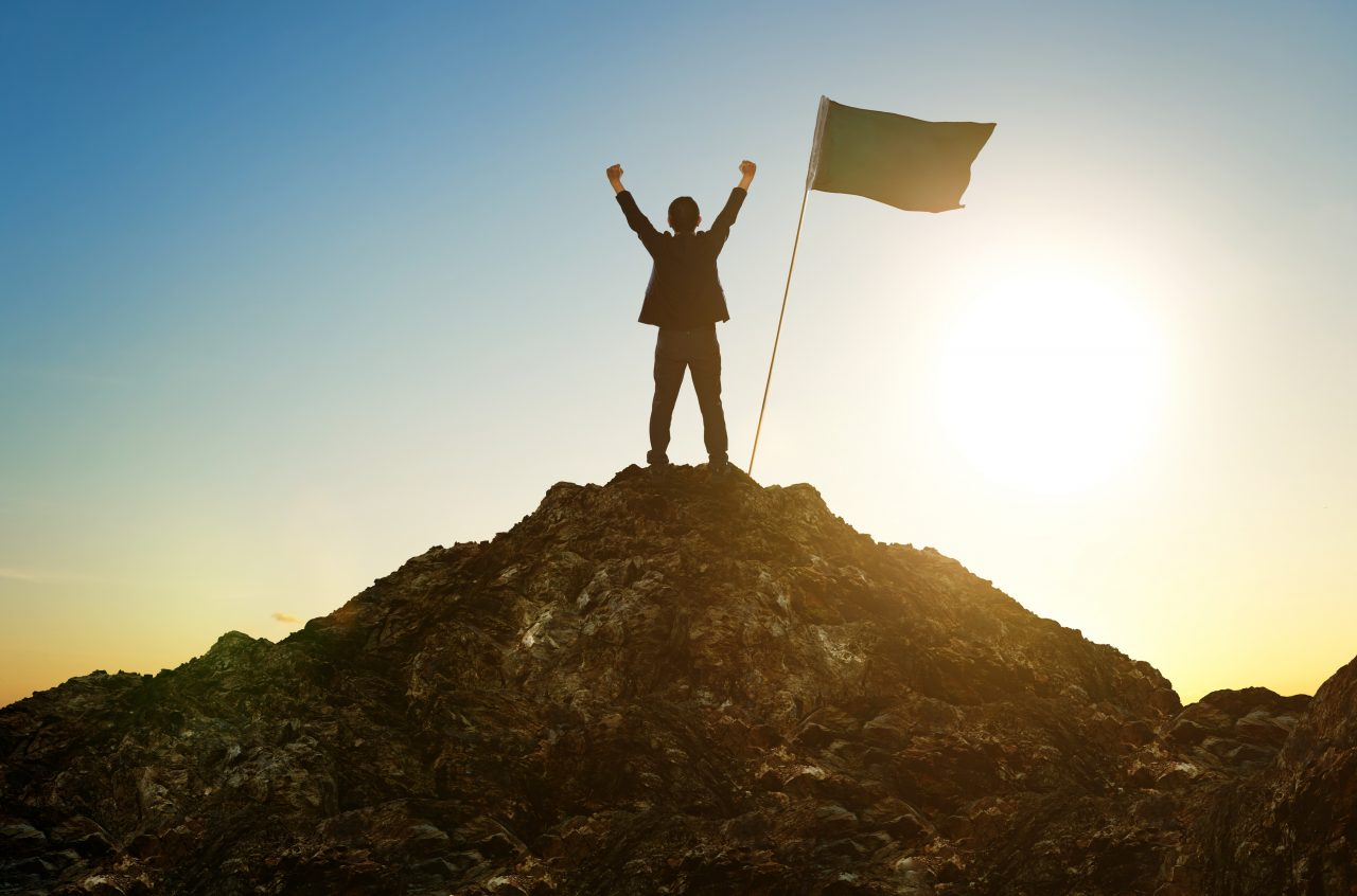 graphicstock-business-success-leadership-achievement-and-people-concept-silhouette-of-businessman-with-flag-on-mountain-top-over-sky-and-sun-light-background_SOllvyhPxjg