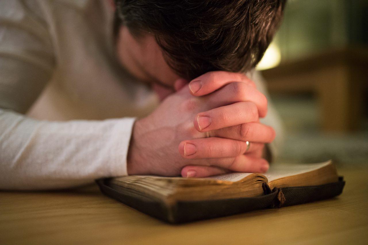 Unrecognizable man praying, kneeling on the floor, hands on Bibl