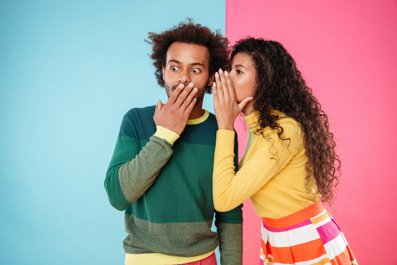 Beautiful curly young woman telling secrets to her boyfriend