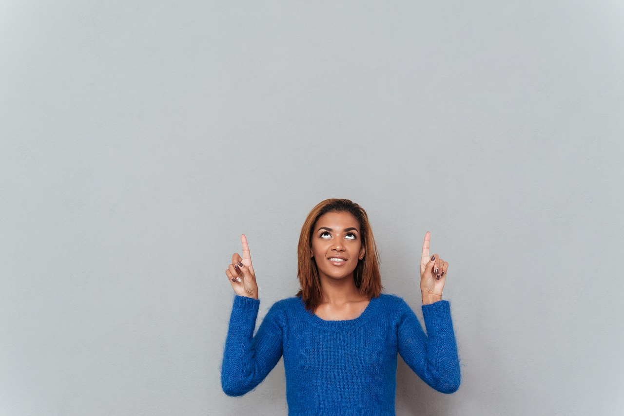 African woman pointing her fingers up